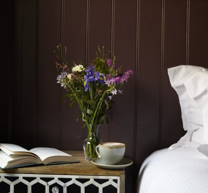 bedside book, coffee and fresh flowers in bedroom at The Archangel, pub and cocktail bar with bedrooms in Frome, Somerset
