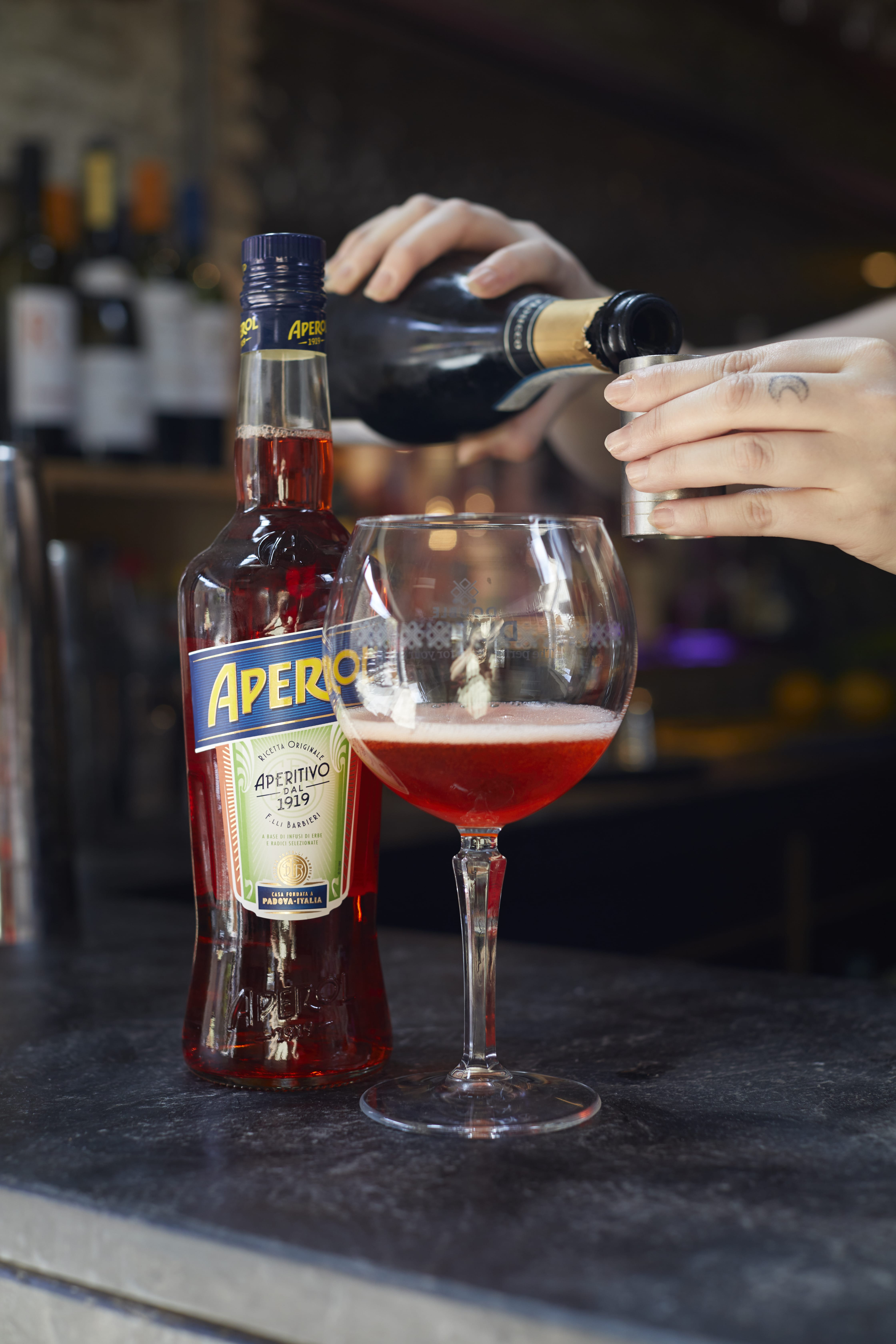 pouring an aperol spritz at the bar at The Archangel, pub and cocktail bar with bedrooms in Frome, Somerset